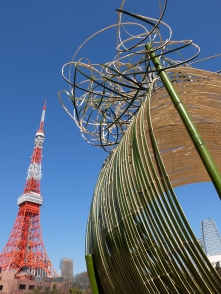 Tokyo tower viewed next to a massive groovy bamboo sculpture in Shiba Koen Park