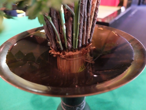 The base of the Rikka arrangement: stems pushed into a straw bundle. Note the wire on all of the stems, covered with brown tape to disguise it.